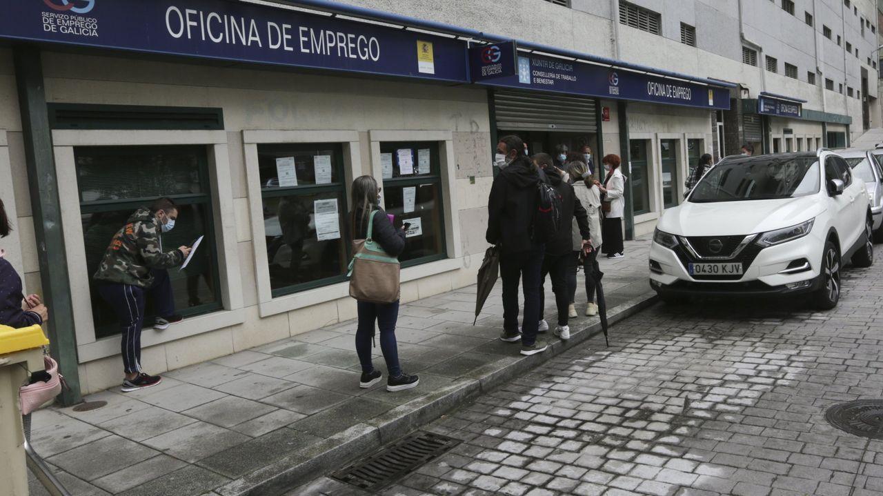 Inauguración del edificio de la Seguridad Spcial, en Viveiro.Un hombre ataviado con una máscara sanitaria pasa frente a una oficina pública de empleo cerrada, en Oviedo.
