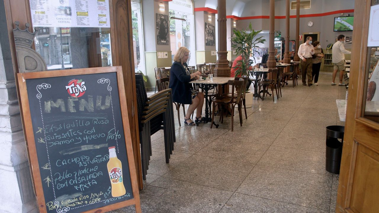 Bañistas en la playa de San Lorenzo de Gijón.Clientes toman un café en el interior de un bar de Gijón este lunes, durante el primer día de la fase 2 de la desescalada