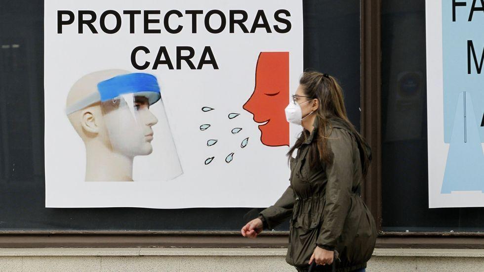 Una mujer pasa delante de un anuncio de pantallas protectoras contra el coronavirus en una calle de Monforte