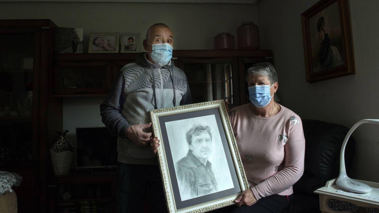 Manuel Moure y su mujer, Toñita, con un retrato de su hijo Manuel