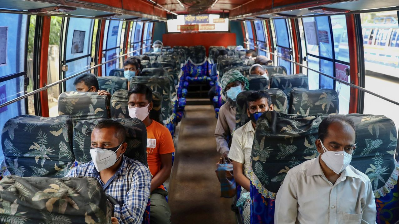 Personas con mascarillas viajan en un bus público en Dacca, Bangladesh