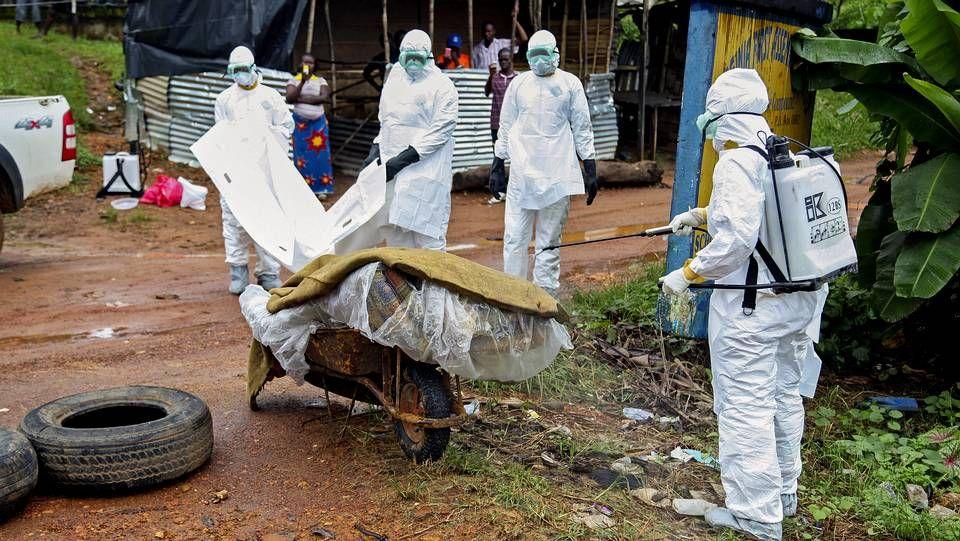 Así es el protocolo ante un caso de ébola. Varias enfermeras liberianas desinfectan una víctima del ébola en la calle en una calle en Virginia, a las afueras de la capital Monrovia, en Liberia