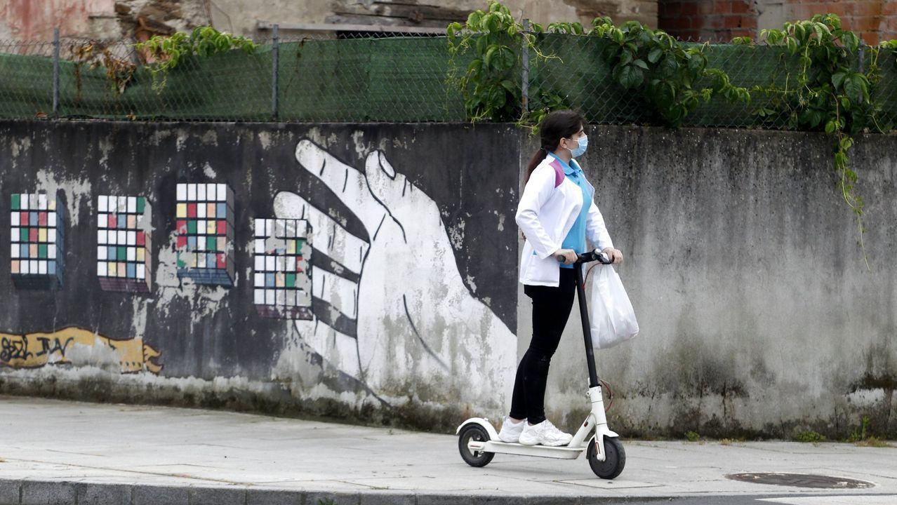 Feijoo comparece tras el comité clínico de expertos sanitarios.Una mujer, en patinete eléctrico y con mascarilla en una calle de Monforte