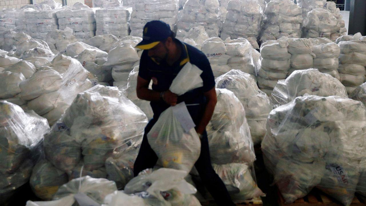 El concierto «Aid Live» reúne a miles de venezolanos en la frontera con Colombia.Un voluntario ordena los paquetes de ayuda en Colombia