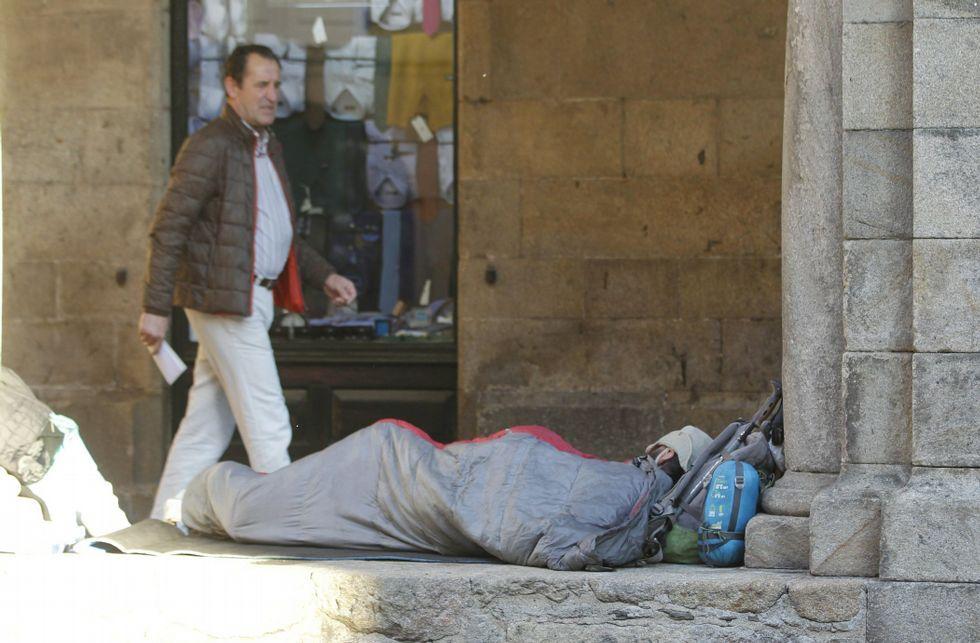 Uno de los indigentes acampados en los soportales de la rúa do Vilar.