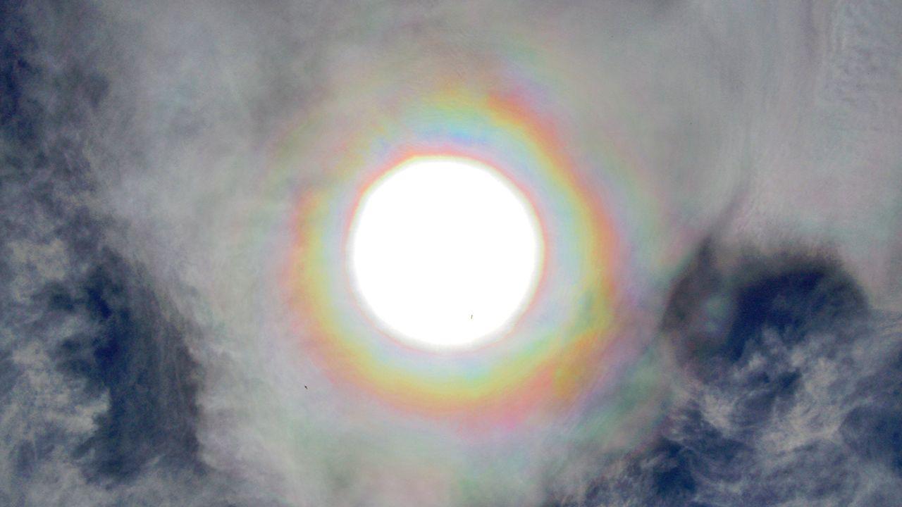 Corona Solar. Paseo del muro de San Lorenzo, Gijón. Se trata de un fenómeno óptico que aparece alrededor del Sol en forma de anillos de colores asemejandose a un arco iris. Las nubes que crean este fotometeoro son nubes formadas por gotas de agua (género Altocumulus)