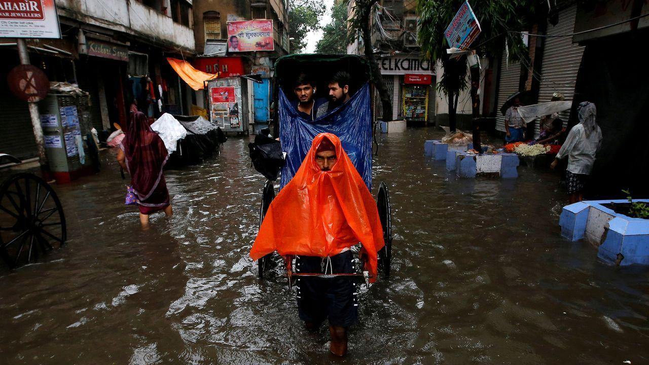Un hombre tira de un carruaje en las calles inundadas de Calcuta