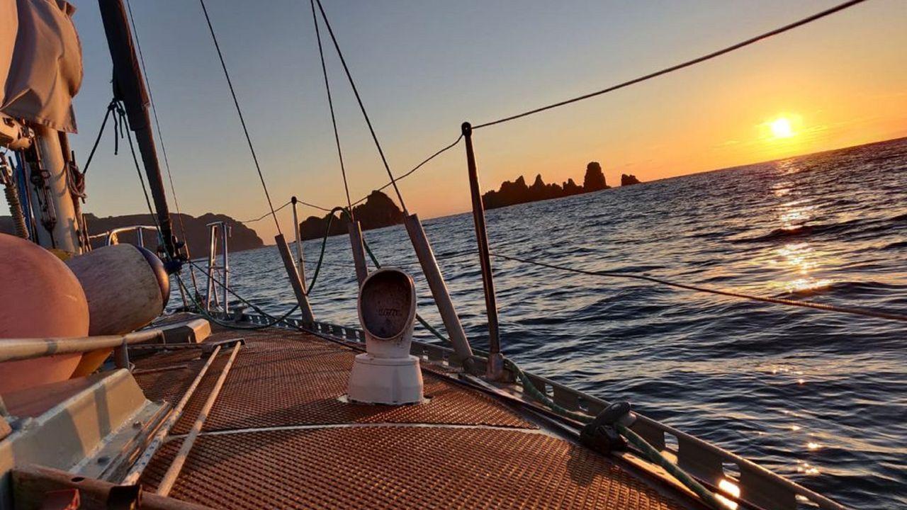 El sol se pone sobre el mar, marcando el perfil de Os Aguillóns y el cabo