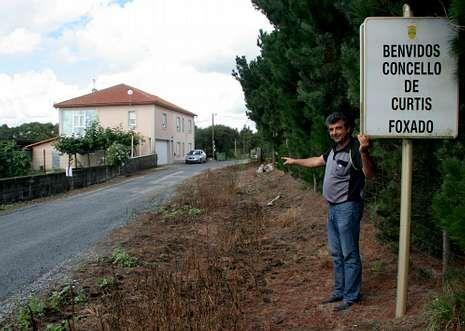 López con la señal de linde mal colocada y el camino sin asfaltar detrás, así como su casa .
