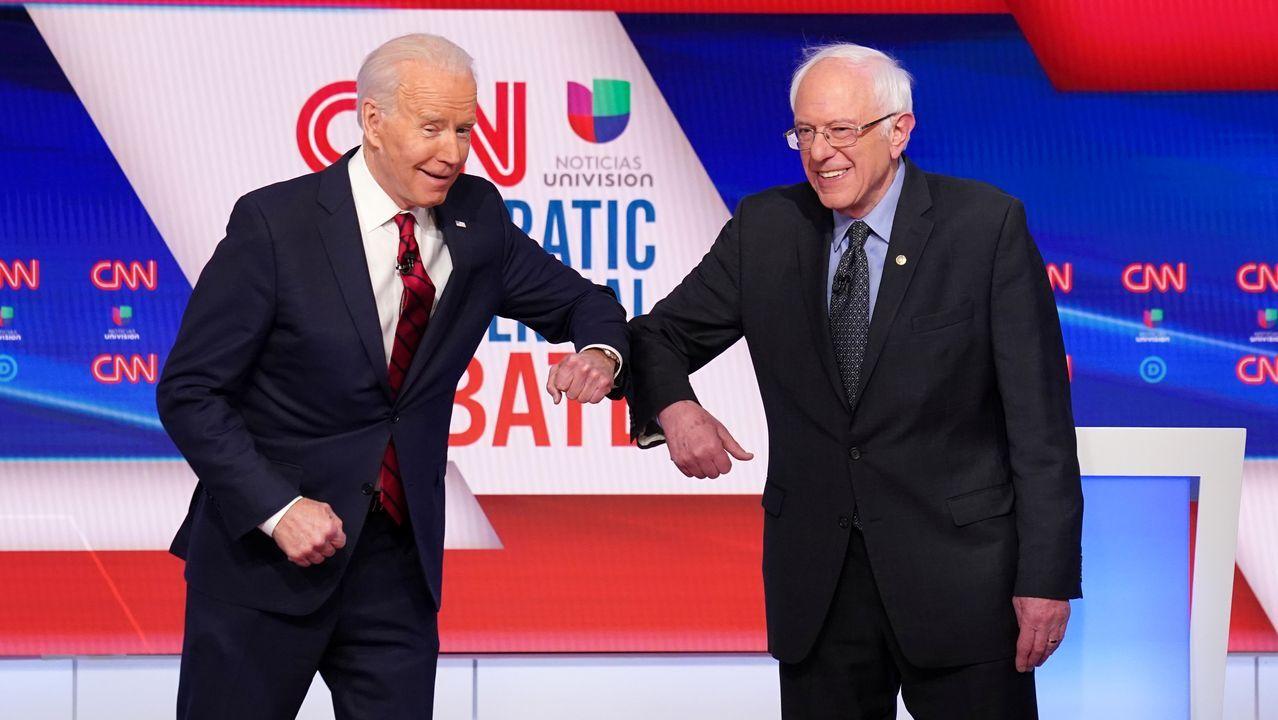 Joe Biden (izquierda) y Bernie Sanders (derecha) chocan el codo antes de su debate por la nominación demócrata a la Casa Blanca