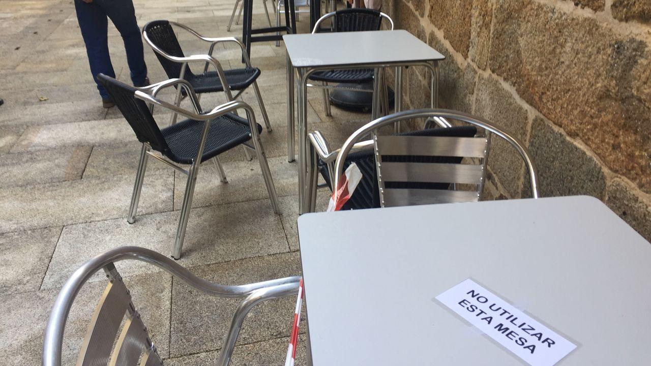 En Celanova, terraza con las mesas señalizadas para cumplir la normativa covid con avisos de que no se pueden utilizar. Están intercaladas: una mesa usable y una precintada