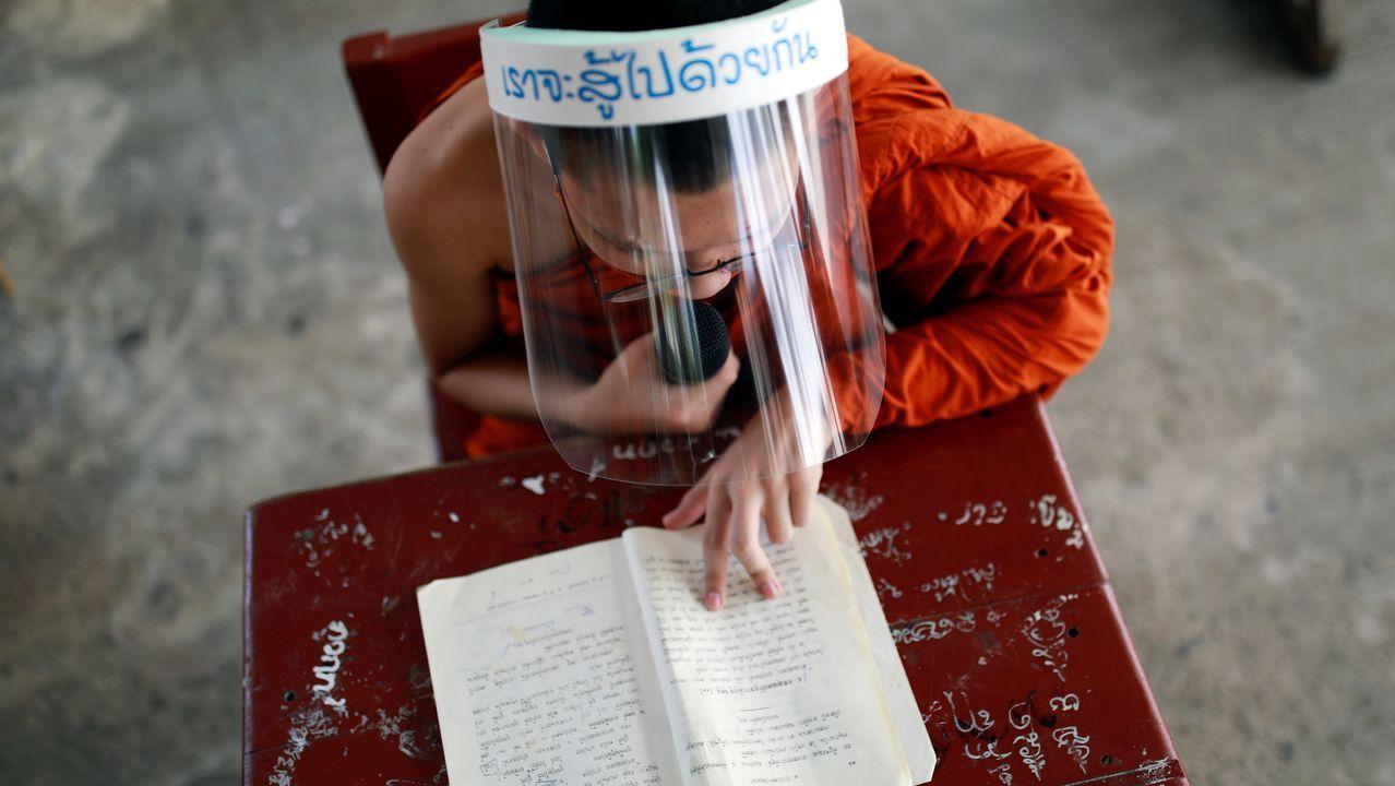 Un monje novato budista con un protector facial y una mascarilla asiste a una lección en el instituto educativo monástico Wat Molilokayaram