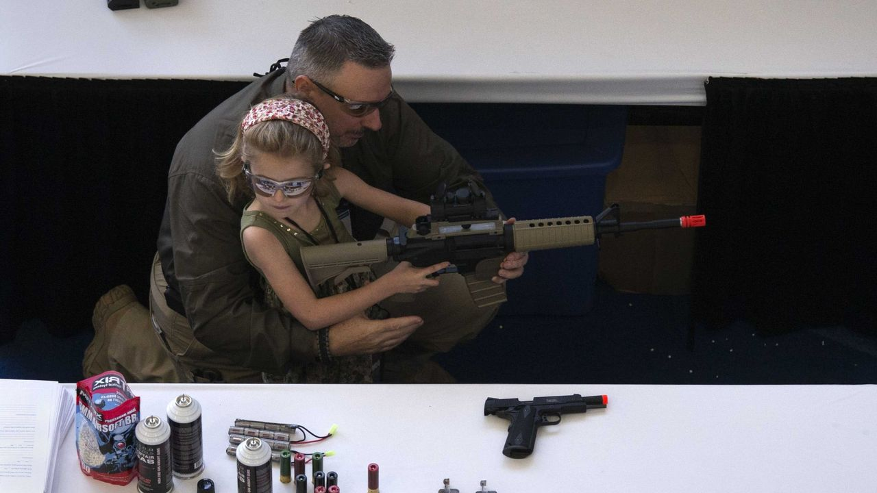 Un hombre muestra a una niña cómo sostener un arma durante la convención anual de la Asociación Nacional del Rifle del 2013, en Houston