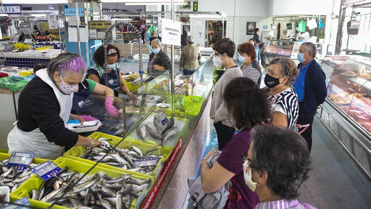 Un pez luna varado en Barraña.Clientes aguardando su turno en la plaza de abastos noiesa