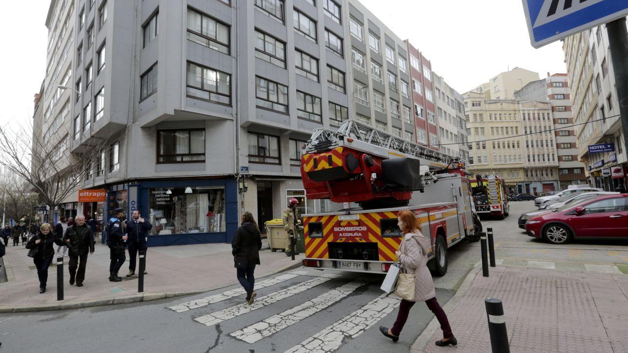 Furgoneta incendiada en la avenida de Os Mallos.Intervención de los bomberos en el edificio