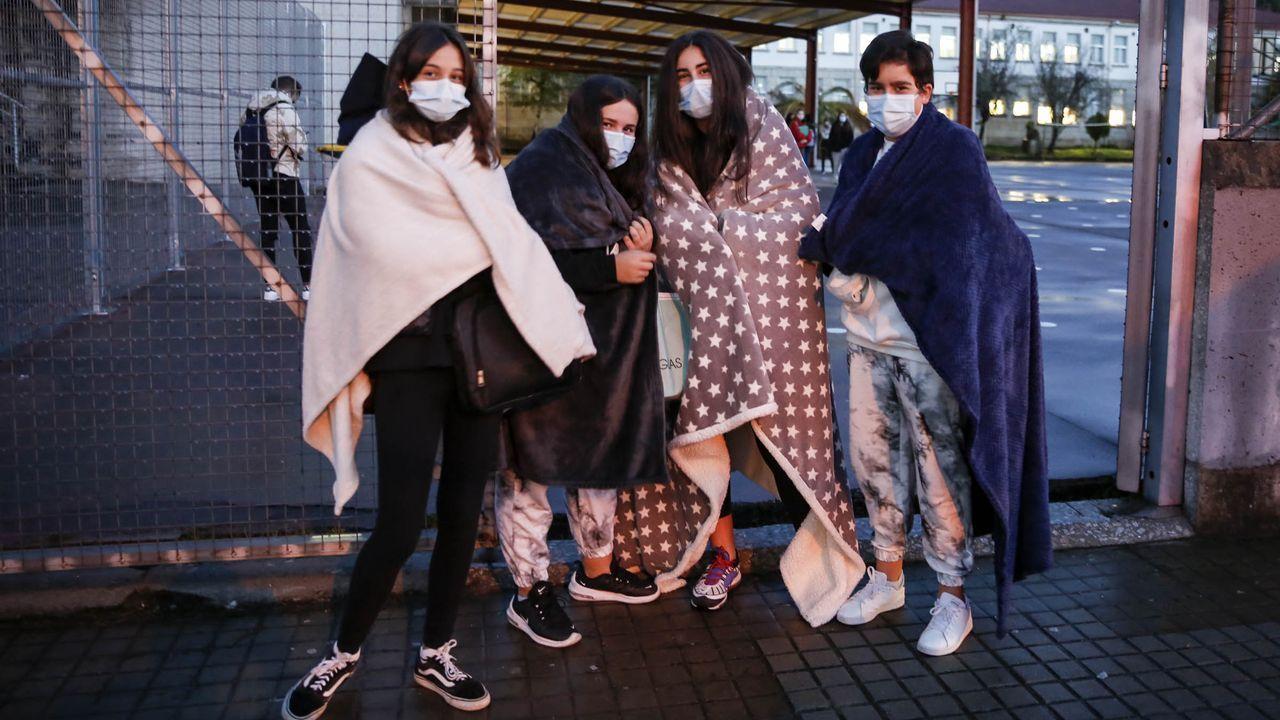 Cuatro de los alumnos del IES O Ribeiro, en el concello ourensano de Ribadavia, portan sus mantas para acudir a clase