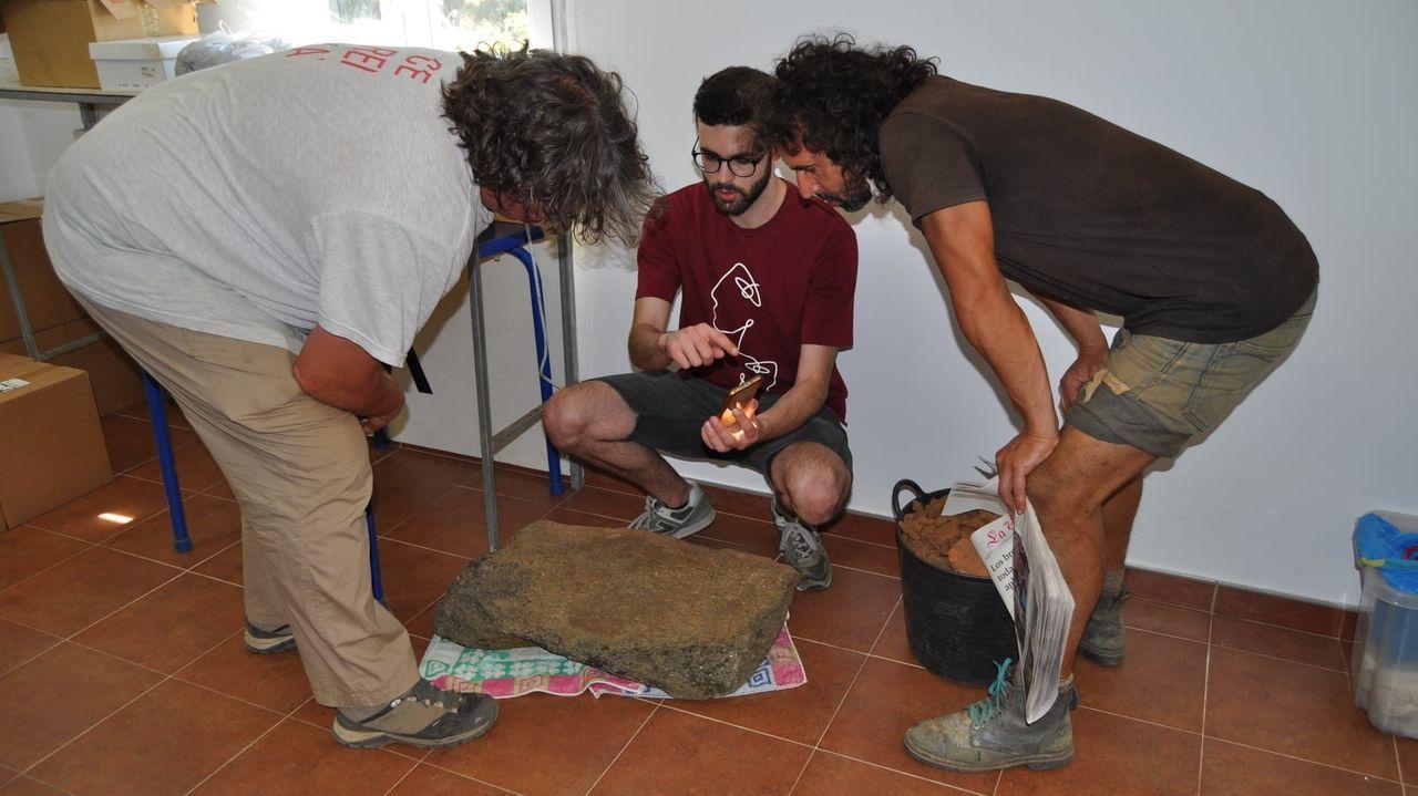 El investigador Álvaro Lorenzo —centro— y los arqueólogos Xurxo Ayán e Iván Aguilera —derecha e izquierda— examinan la lápida sepulcral descubierta en Vilachá de Salvadur