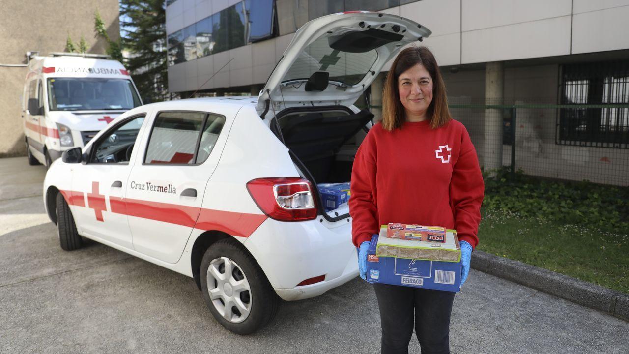 Una voluntaria de Cruz Roja reparte alimentos a las familias afectadas por la crisis en Santiago