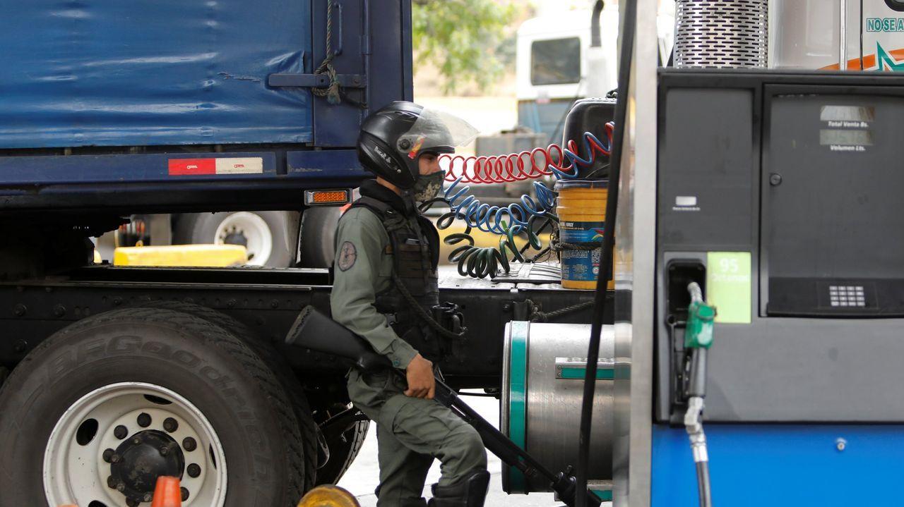 Un miembro de la Guardia Nacional Bolivariana vigila el abastecimiento de combustible en una estación de servicio de Caracas