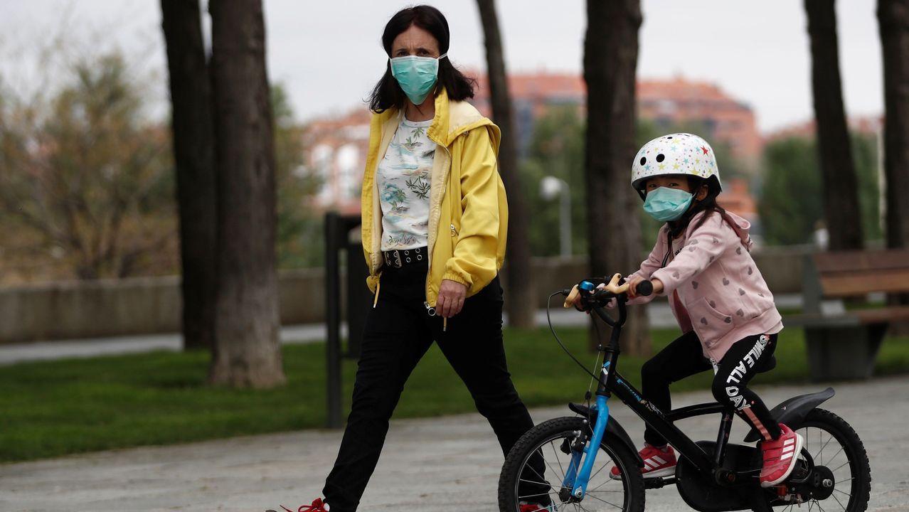 Una madre y su pequeña en bicicleta pasean por Madrid, este domingo