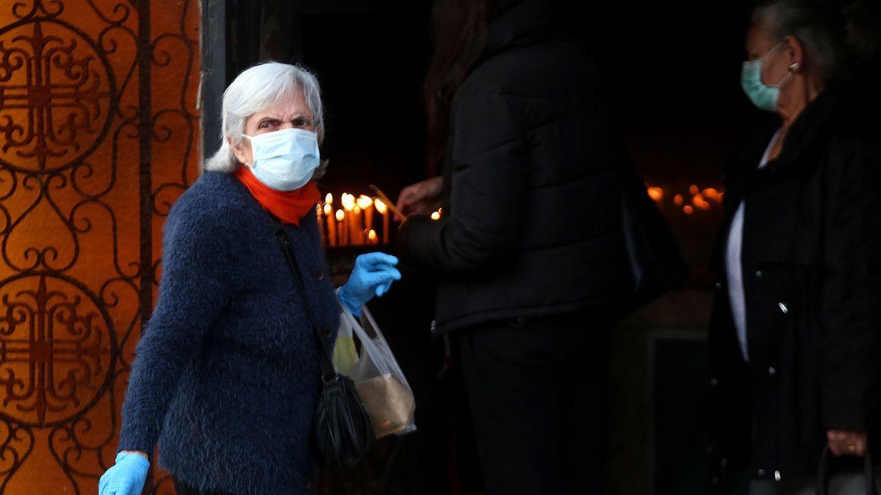 Peregrinos griegos portan mascarillas y guantes para asistir al oficio del Buen Viernes en Atenas