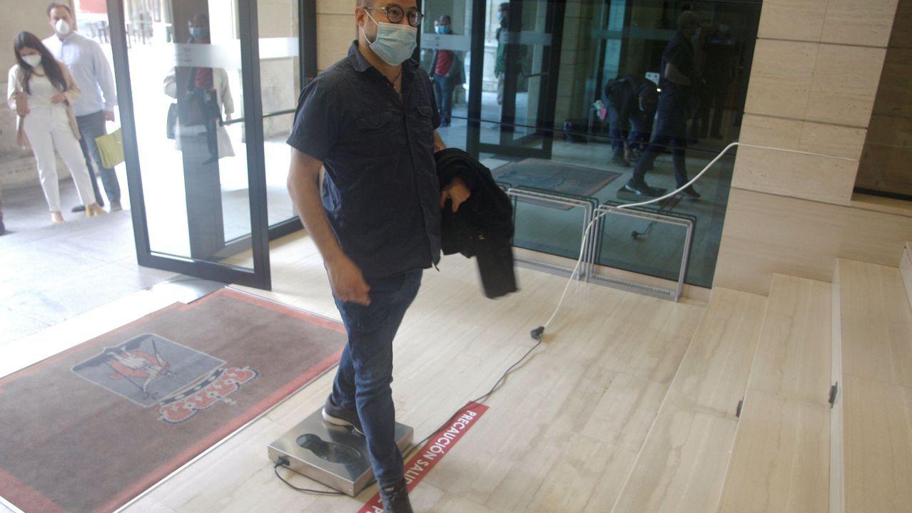 Un ciudadano entra en el Ayuntamiento de Gijón con mascarilla y tras utilizar un nuevo sistema para descontaminar zapatos de COVID-19