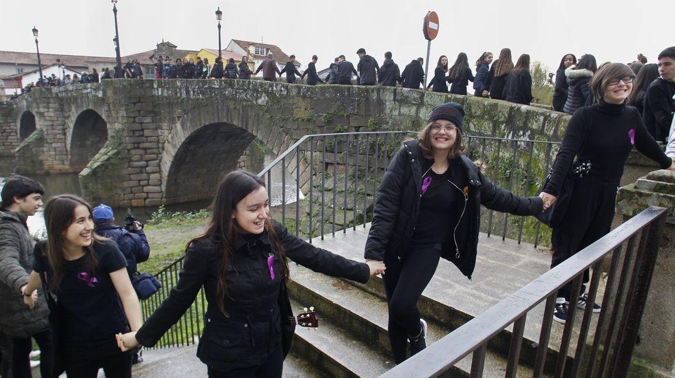 Estudiantes vestidas de negro en la cadena humana que unió este lunes los puentesnuevo y viejo en Monforte