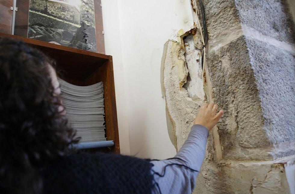 Una informadora turística enseña los efectos de la humedad en una de las paredes.