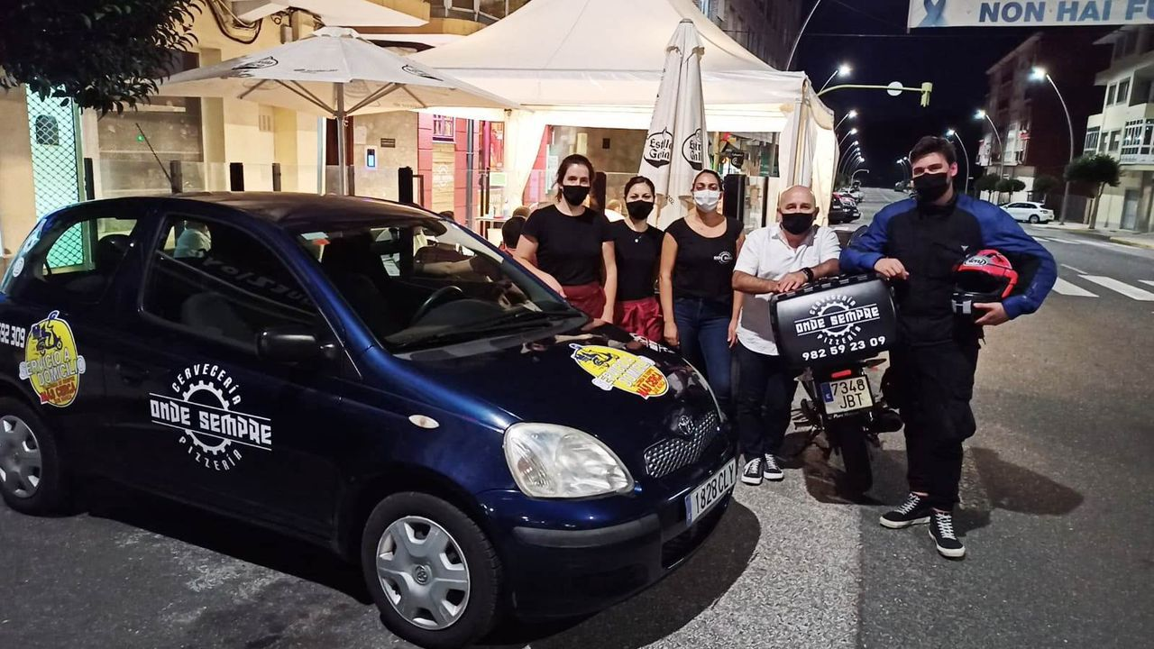 De blanco, Juan Carlos López, propietario de Onde Sempre, con su personal y el coche y la moto para reparto