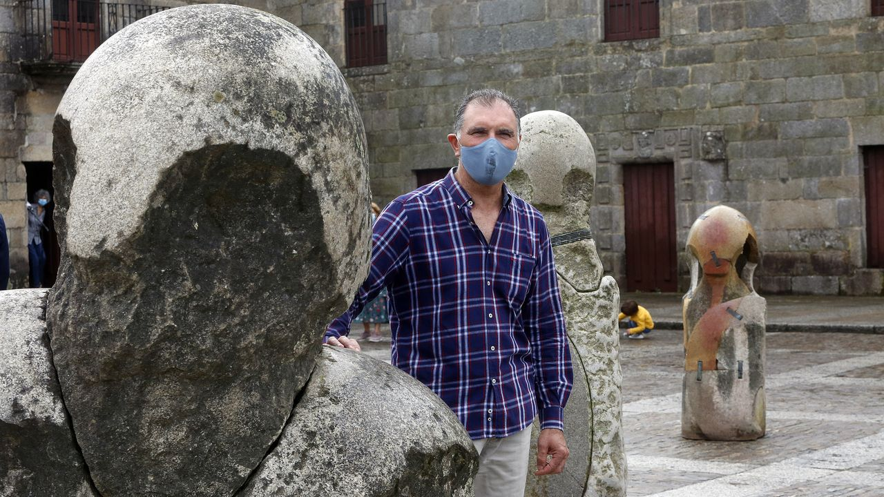 El escultor Francisco Pazos posa en la plaza de Fefiñáns con una de sus piezas