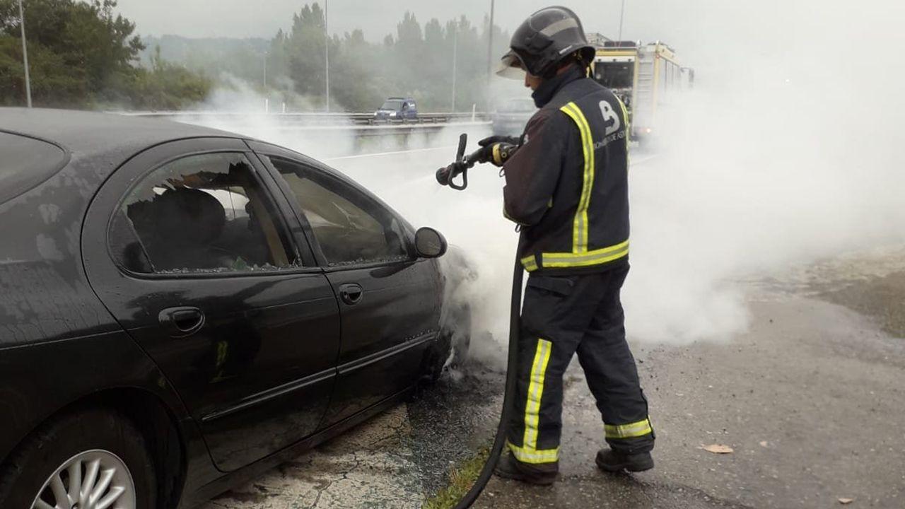 Bombero sofocando el incendio en un coche averiado en la «Y»