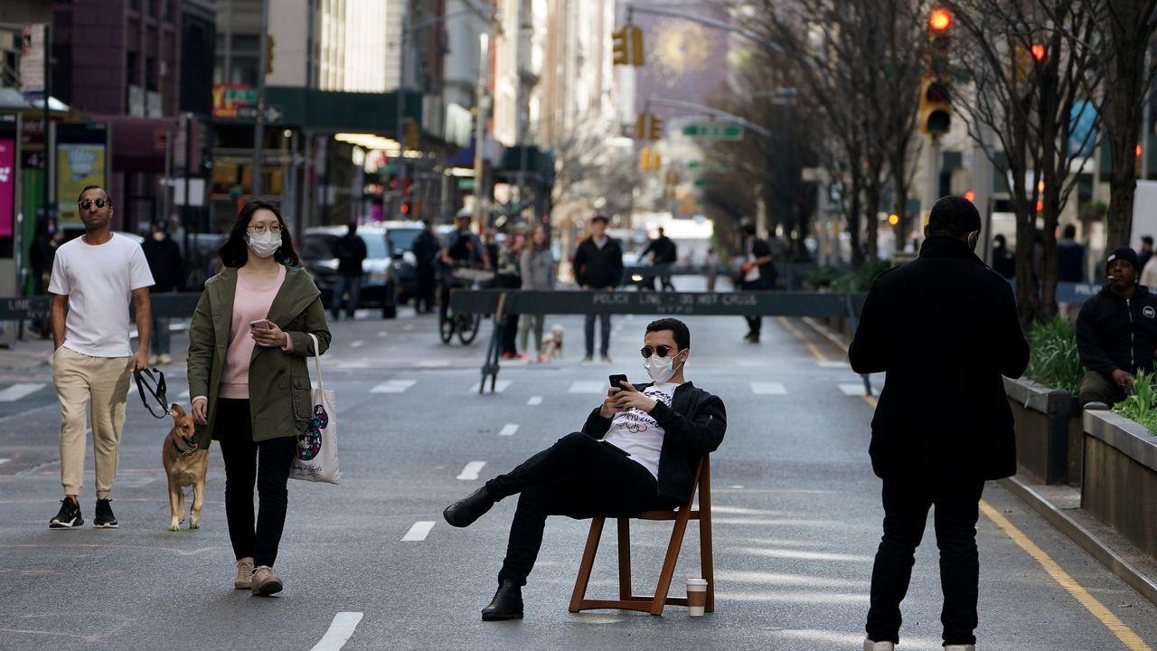 Un hombre permanece sentado en Park Avenue, cortada a causa del coronavirus.