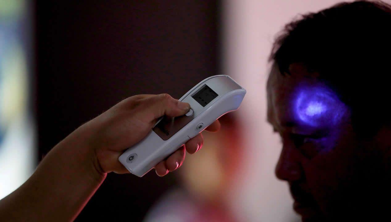 Trabajadores del Ministerio de Salud revisan la temperatura de pasajeros provenientes de un vuelo de España el 2 de marzo