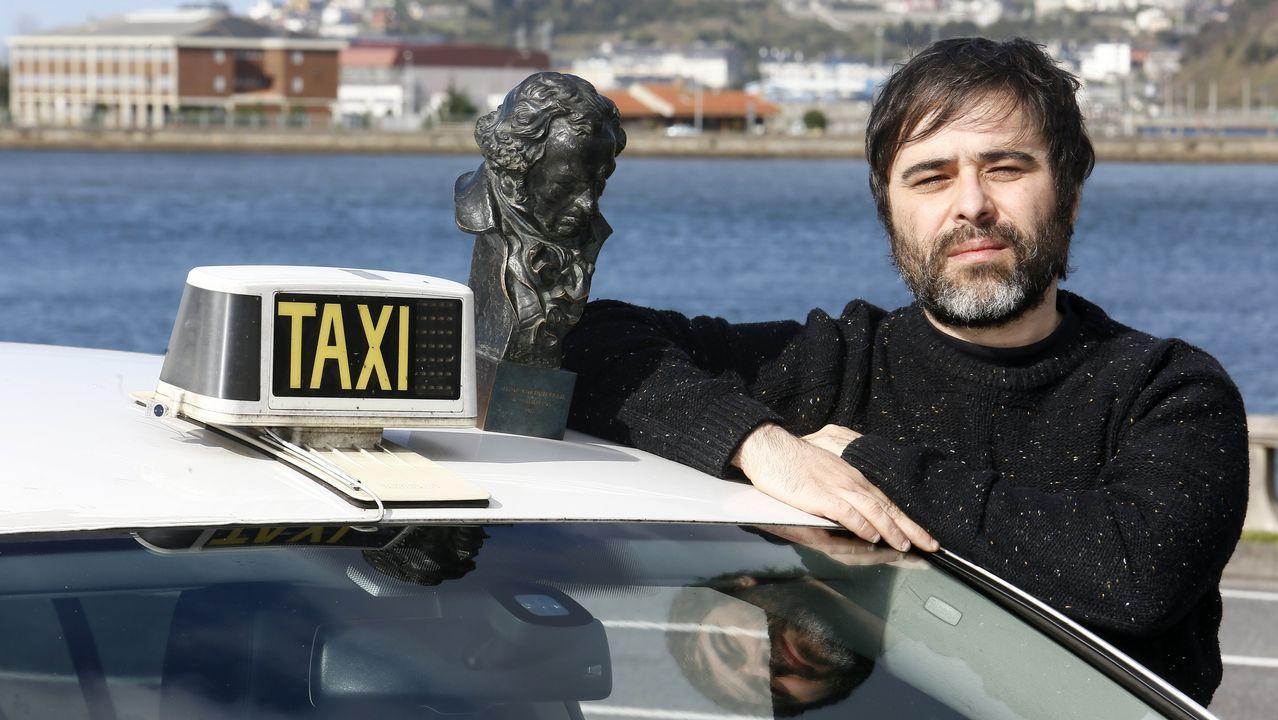 Víctor García, junto al taxi que conduce en Viveiro, y uno de los dos Goyas que ha ganado