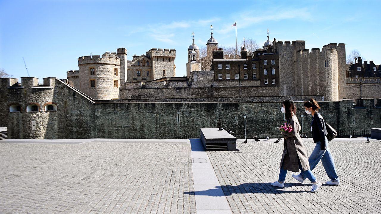 Dos mujeres con máscaras de protección pasean frente a la Torre de Londres.