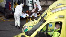 Un trabajador de ambulancias con los epis lleva a un paciente de covid al hospital vizcaíno de Cruces.