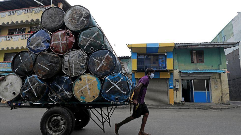 Un hombre con mascarilla tira de un carro en Colombo, Sri Lanka