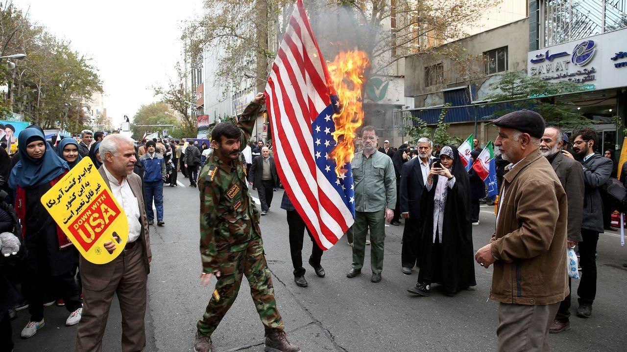 Un iraní quema una bandera de EE.UU. en una calle de Teherán