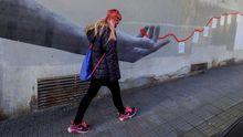 Una mujer pasa por delante de un mural en Siero