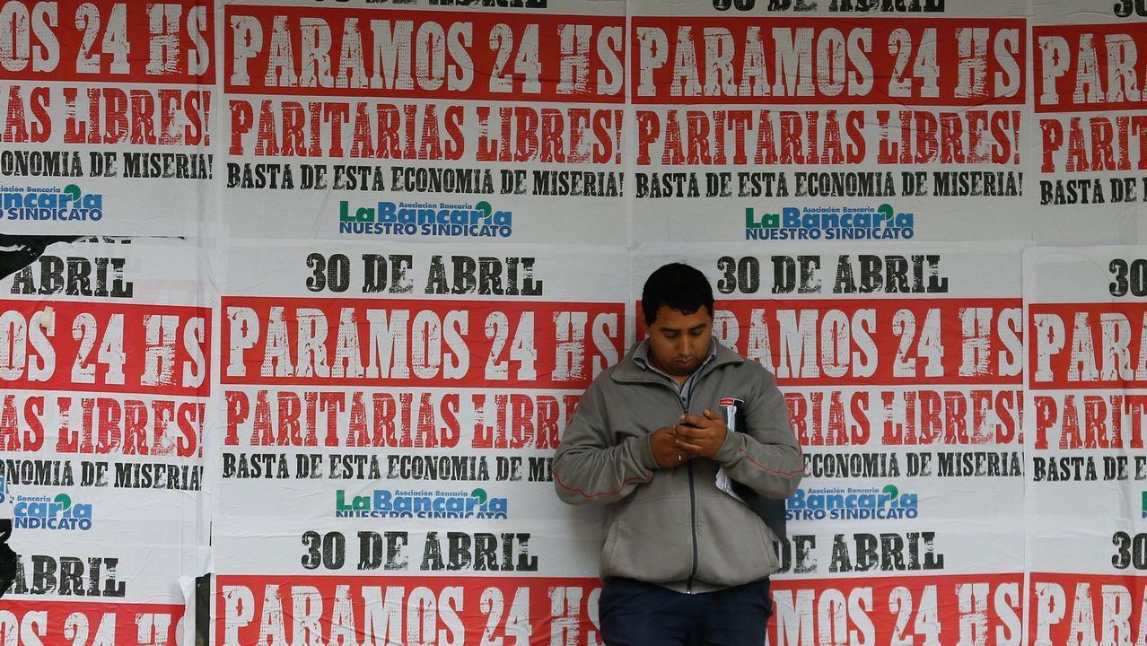 mama. Un hombre mira un teléfono en un muro con carteles que llaman a la huelga general