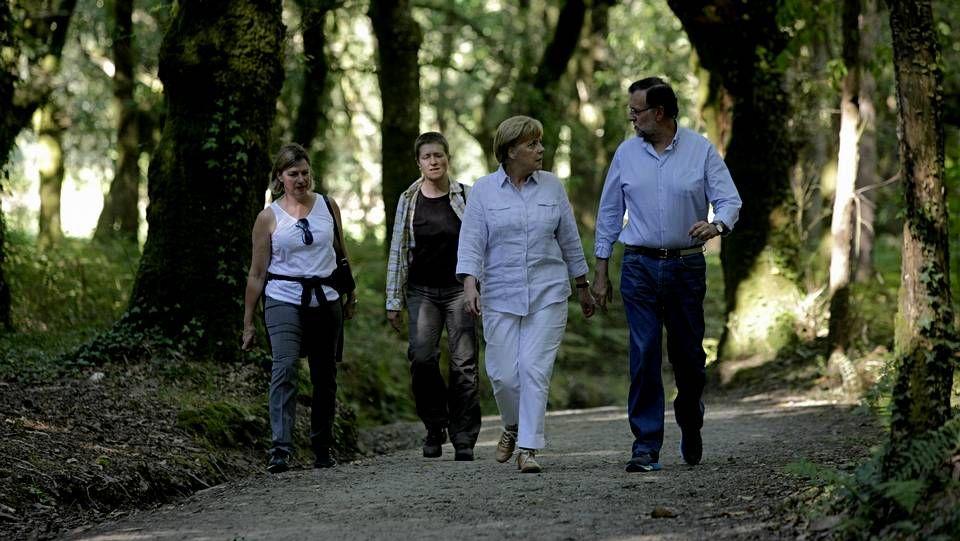 Rajoy muestra Santiago a Merkel.Merkel y Rajoy conversan durante la caminata desde O Pino