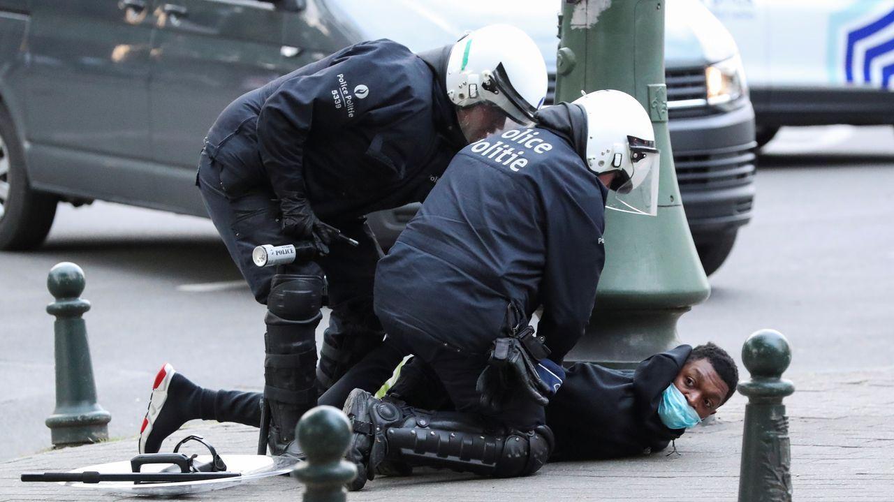 Policias belgas detienen a un manifestante durante las protestas del domingo