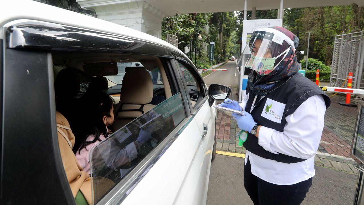 Un trabajador revisa la temperatura de los visitantes del jardín botánico de Bogor, Indonesia, en su primer día de reapertura