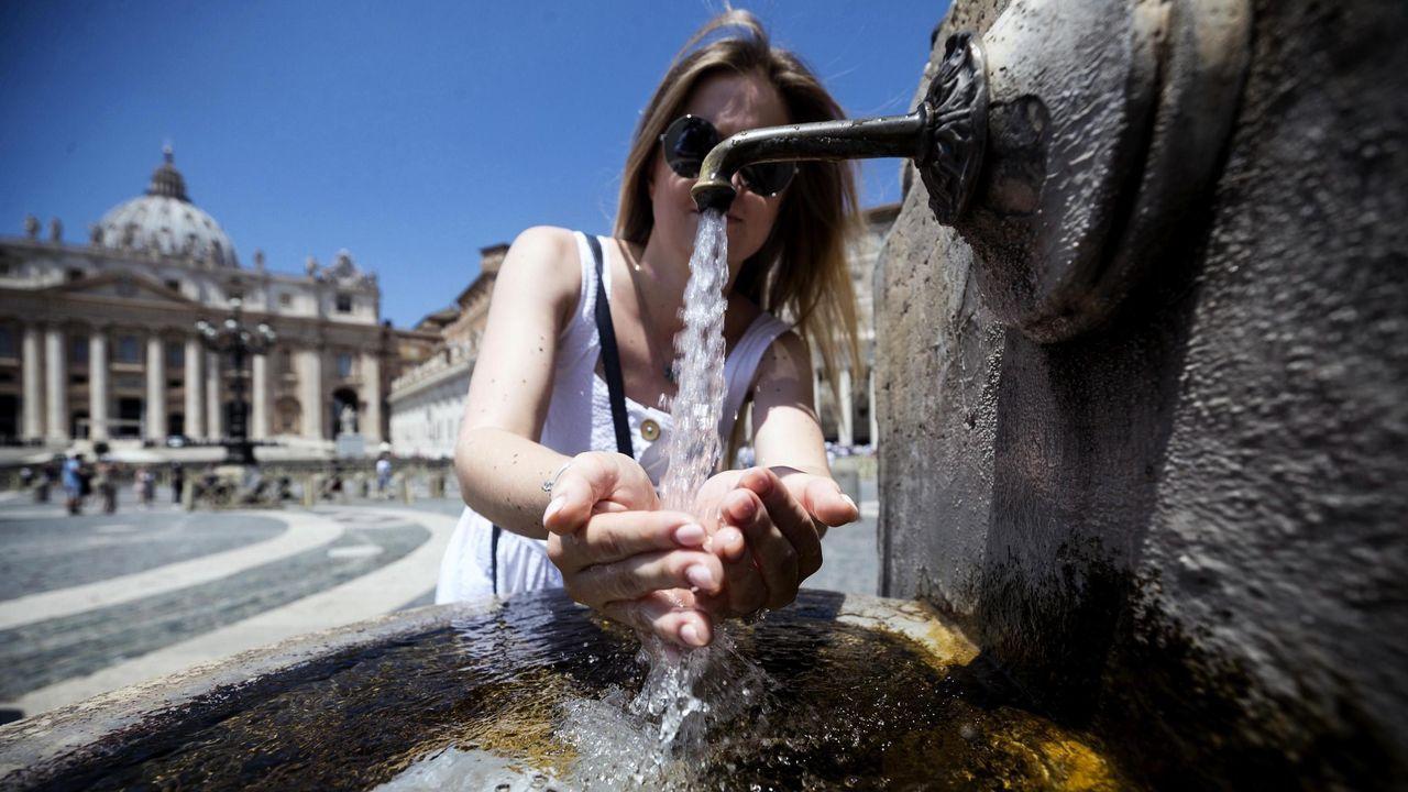 Una viandante se refresca en una fuente del centro de Roma