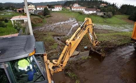 Una pala retroexcavadora retiró los restos depositados en un vial próximo a las casas del lugar malpicán de Aviño.