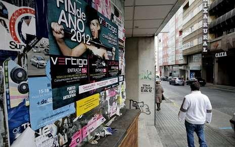 Los carteles promocionando fiestas de Nochevieja inundan muros y farolas de la ciudad.