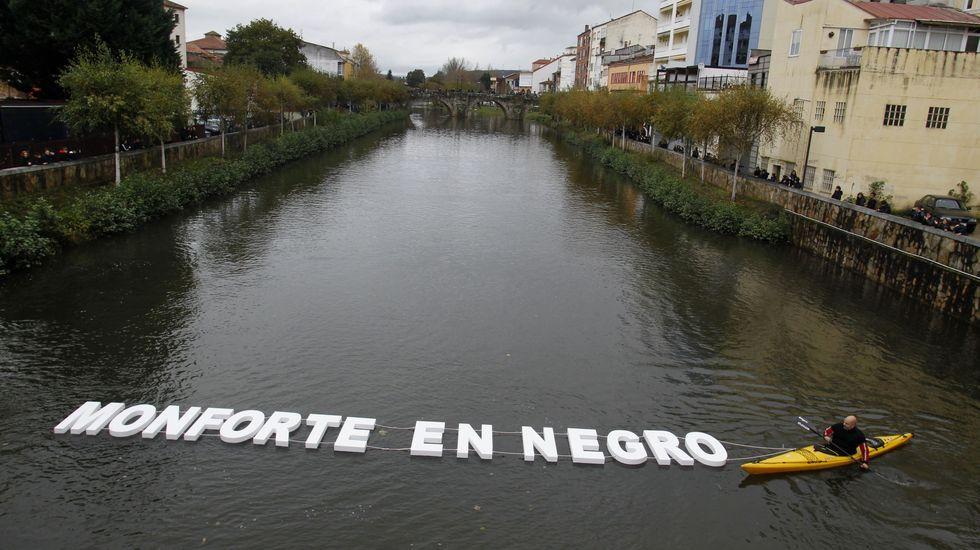 Dos piragüistas del club Quixós mostraron en Monforte en el río Cabe la frase  Monforte en negro  formada por grandes letras blancas