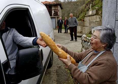 Concepción compra el pan ante la atenta mirada de su esposo y vecinos.