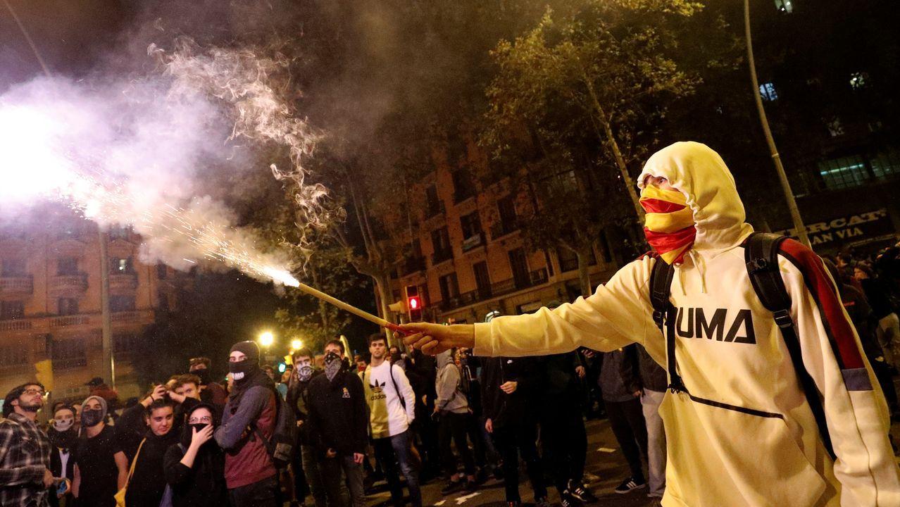 Uno de los manifestantes, con el rostro oculto bajo una máscara, ante una de las barricadas en llamas
