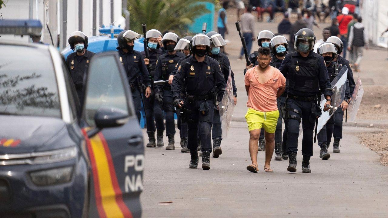 Policías antidisturbios trasladan a un detenido del campamento humanitario de Las Raíces